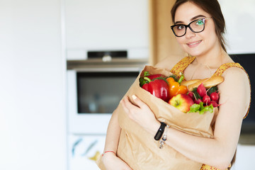 Young woman holding grocery shopping bag with vegetables