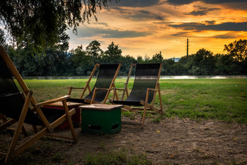 Chairs and primitive table by the river at sunset