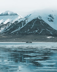 Boat moored on frozen sea against snowcapped mountains