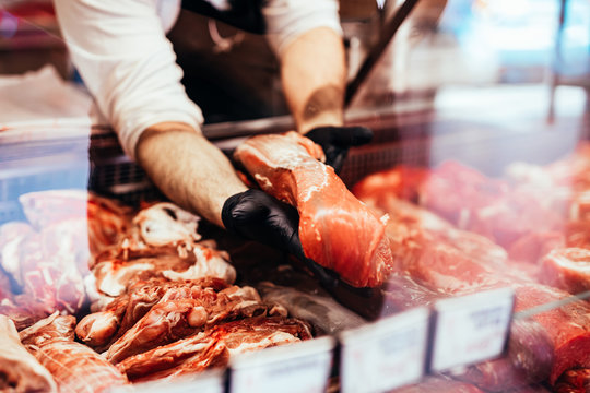 Close up on butcher's hands in gloves working in butchery.