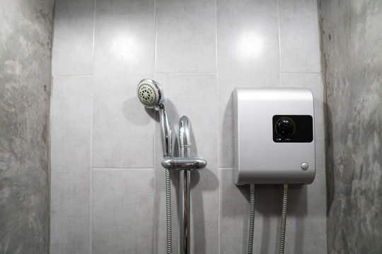 Instant tankless electric water heater installed on grey tile wall with input and output pipe/outlet and elcb safety breaker system and silver shower.