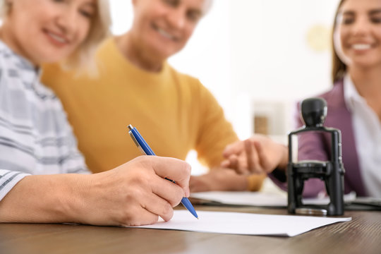 Mature couple signing document in notary's office, closeup