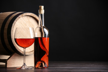 Wooden cask, bottle and glass of wine on table against dark background, space for text
