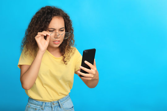 Young African-American woman with vision problems using smartphone on blue background