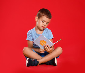 Cute little boy reading book on red background