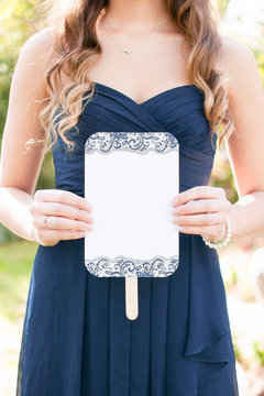 young bridesmaid wearing a navy dress and long hair holding a blank wedding ceremony program fan, wedding itinerary, copyspace, blank card