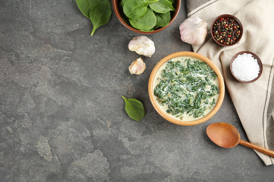 Tasty spinach dip on grey table, flat lay. Space for text