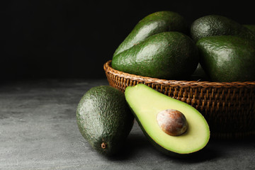 Delicious ripe avocados on grey table against dark background