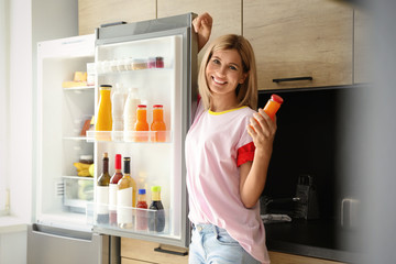 Woman with bottle of juice near refrigerator in kitchen
