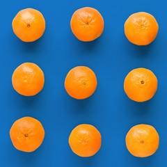 Fruit pattern of fresh orange tangerine or mandarin on blue background. Flat lay, top view. Pop art design, creative summer concept. Citrus in minimal style.