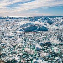Iceberg and ice from glacier in arctic nature landscape on Greenland. Aerial photo drone photo of icebergs in Ilulissat icefjord. Affected by climate change and global warming.
