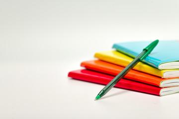Pila de libretas de colores con pluma