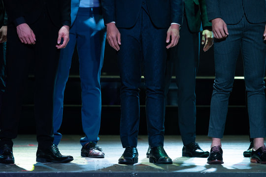 Group of Business men on Stage Ramp with purple led light and show Legs parts only.  Many proper English Slack pants with Brogue leather shoes under low exposure, shadow and noise