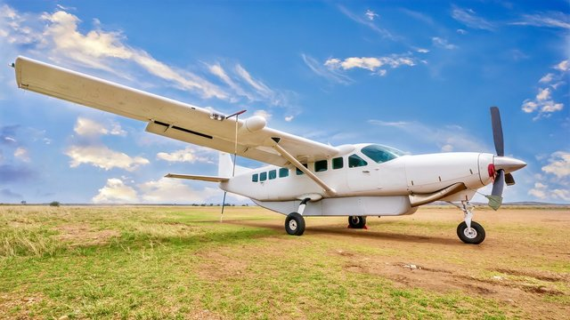 A white, single engine charter plane sits on a grass and dirt landing strip in a beautiful and remote location in Kenya