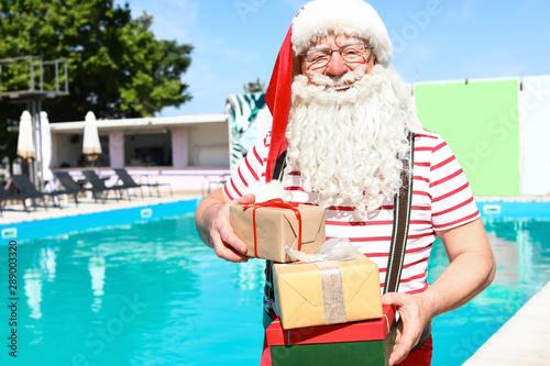 Santa Claus with gifts near swimming pool at resort\