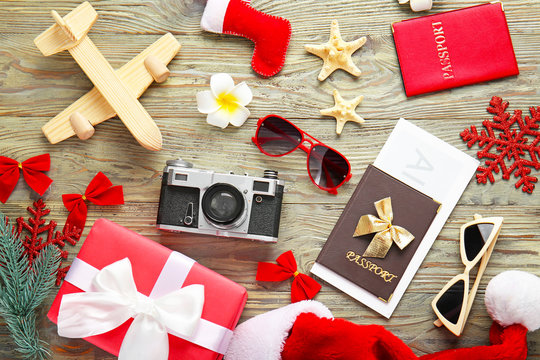 Composition with gift box, passports, ticket and photo camera on wooden background. Christmas vacation