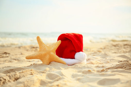 Santa Claus hat with starfish on sea coast. Christmas vacation