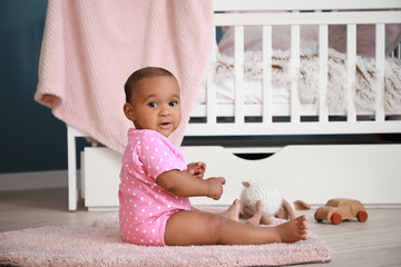 Portrait of cute African-American baby at home