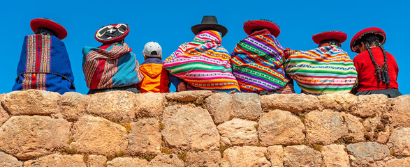 Panoramic photograph of Quechua indigenous women in traditional clothing with a boy sitting on an ancient Inca wall in Chinchero, Cusco Province, Peru. Fototapete