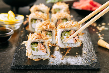 Macro Shot of Eating Katsuobushi Uramaki Sushi Rolls with Fried Salmon