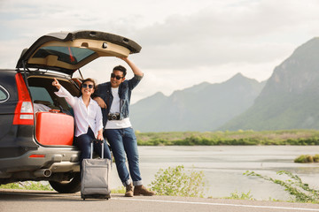 Asian couple Man with vintage camerra and woman sitting on back of car  travel to mountain and lake...