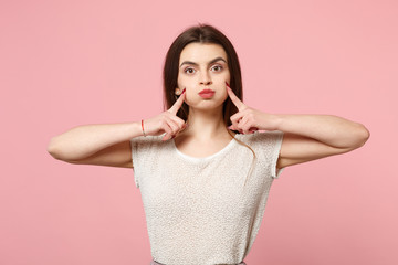 Young woman in casual light clothes posing isolated on pink wall background, studio portrait. People sincere emotions lifestyle concept. Mock up copy space. Pointing index fingers on blowing cheeks.