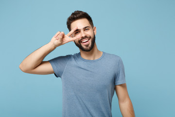 Young smiling joyful handsome man in casual clothes posing isolated on blue wall background, studio portrait. People sincere emotions lifestyle concept. Mock up copy space. Showing victory sign.