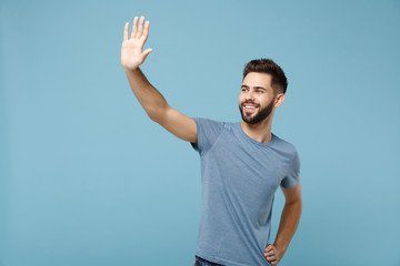 Young smiling man in casual clothes posing isolated on blue wall background in studio. People sincere emotions lifestyle concept. Mock up copy space. Waving and greeting with hand as notices someone.