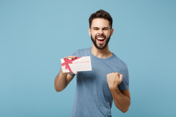 Young happy man in casual clothes posing isolated on blue wall background, studio portrait. People sincere emotions lifestyle concept. Mock up copy space. Hold gift certificate, doing winner gesture.