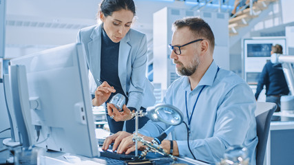 Female Industrial Engineer Talks with Electronics Specialist, She Holds Metal Component Prototype, he Works on Computer. Modern and Bright Office with Stylish People