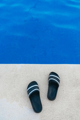 Rubber flip flops on edge of pool
