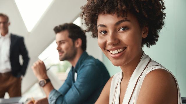 Feeling happy. Young afro american woman is looking at camera and smiling while working with colleagues together at office
