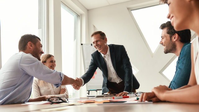 Congratulations Two cheerful colleagues shaking hands and smiling while sitting in the modern office