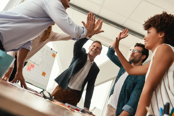Success Business people giving each other high-five and smiling while working together in the modern office