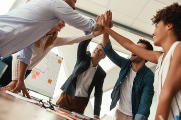 We did it Business people giving each other high-five and smiling while working together in the modern office