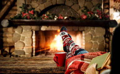 Woman legs with christmas socks and fireplace