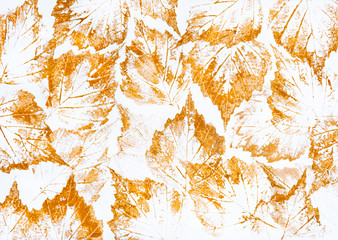 Imprints of yellow autumn leaves on a white background. Texture made with golden acrylic paint on paper
