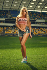 Athletic girl with big breasts at the stadium. The beautiful blonde.