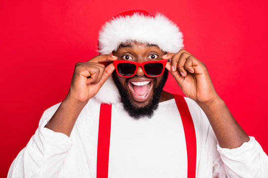 Close up photo of astonished african santa claus touching his specs screaming wow omg see noel miracle wearing stylish white sweater isolated over red background