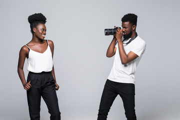 Young african man photographer taking photo of african woman on camera isolated on gray background