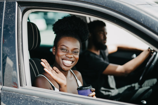 Smiling african couple in car with coffee. Young african girl looking at camera and greeting someone while drink coffee. African man at the wheel drive car
