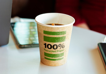 a recycled paper container containing hot coffee for a break.