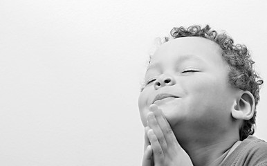 boy praying to God stock image with hands held together on white background stock photo