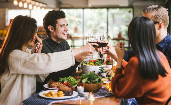 Dinner with friends. Group of young people enjoying dinner together. Dining Wine Cheers Party thanksgiving Concept