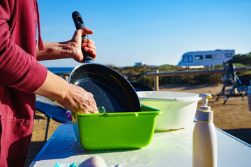 Woman washing dishes in bowl, capming outdoor