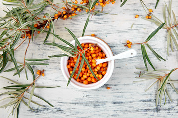 Natural, organic sea buckthorn berry in bowl and a on white wooden background. Branch of sea buckthorn. Top view.