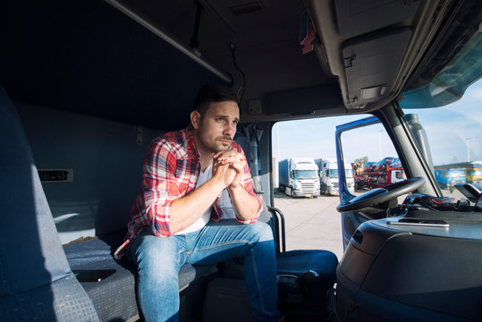 Truck driver sitting in his cabin and thinking about his family. Trucker missing his family being sad. Truck driver lifestyle.