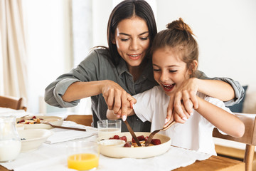Image of amazing family mother and little daughter eating together while having breakfast at home in morning