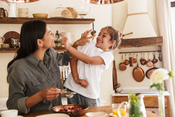 Image of cheerful family woman and her little daughter cooking together meal with raspberry at cozy apartment