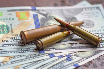 Weapon bullets on American dollars background. Military industry, war, global arms trade and crime concept.